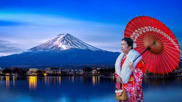Azjatycka kobieta ubrana w tradycyjne japońskie kimono na górze fuji, jezioro kawaguchiko w japonii.