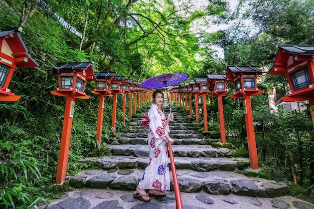 Azjatycka kobieta ubrana w tradycyjne japońskie kimono w kifune shrine w kioto w japonii.