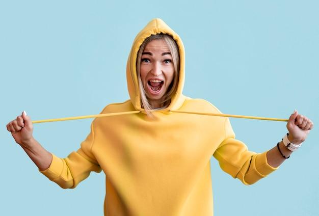 Azjatycka kobieta ubrana w żółtą bluzę z kapturem na niebieskim tle