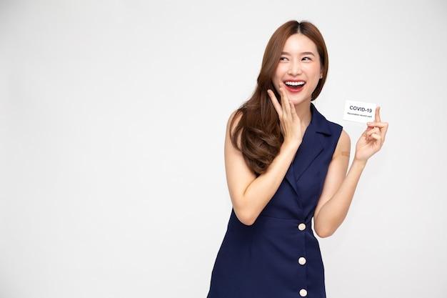 Azjatycka kobieta uśmiecha się i pokazuje kartę szczepień przeciwko covid19 na białym tle