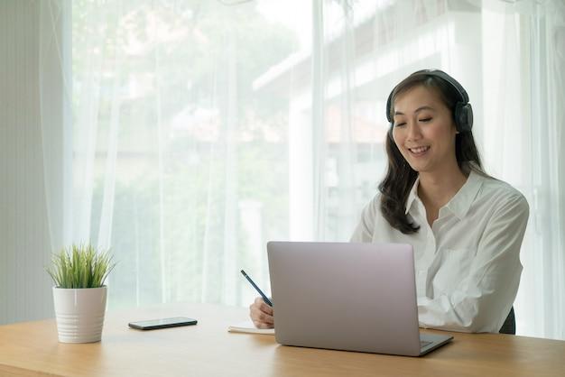 Azjatycka kobieta uśmiecha się i rozmowa wideo online z komputera przenośnego, ostrzegając bezprzewodowe słuchawki i robiąc notatki przy biurku.