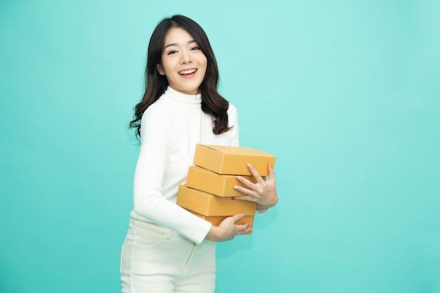 Azjatycka kobieta uśmiecha się i trzyma pudełko paczek na białym tle na jasnozielonym.