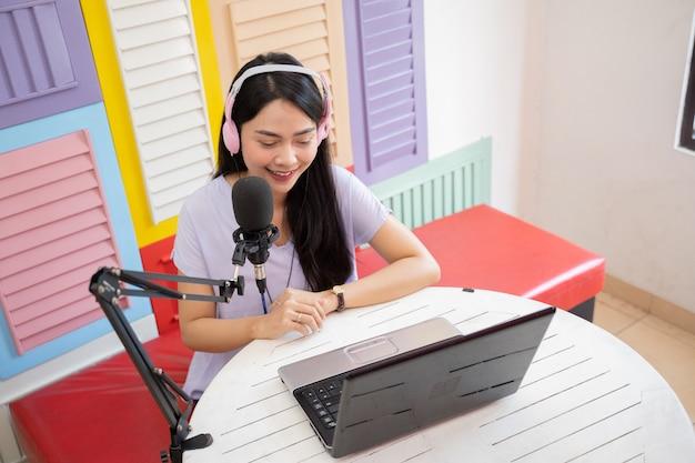 Azjatycka kobieta uśmiecha się siedząc w słuchawkach i używając laptopa