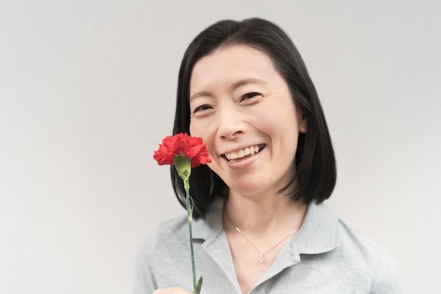 Azjatycka kobieta uśmiecha się z goździkiem i bielą