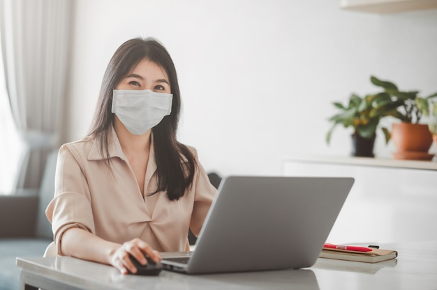 Azjatycka kobieta uśmiechająca się podczas noszenia maski na twarz pracująca w domu z laptopem podczas kwarantanny koronawirusa