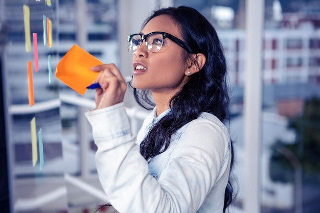 Azjatycka kobieta usuwa kleistą notatkę szklaną ścianą