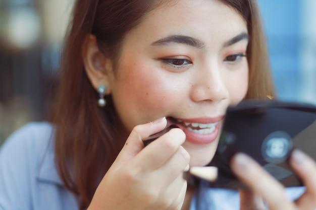 Azjatycka kobieta uzupełniał jej twarz z pomadką w kawiarni