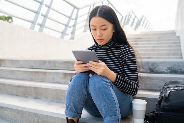 Azjatycka kobieta używa cyfrową pastylkę.