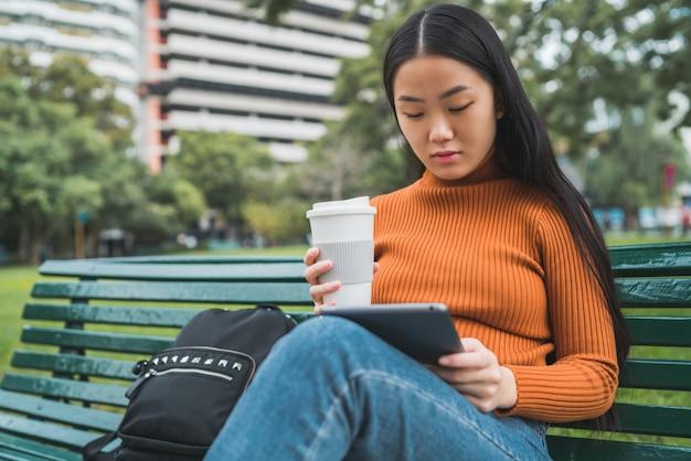 Azjatycka kobieta używa jej cyfrową pastylkę.