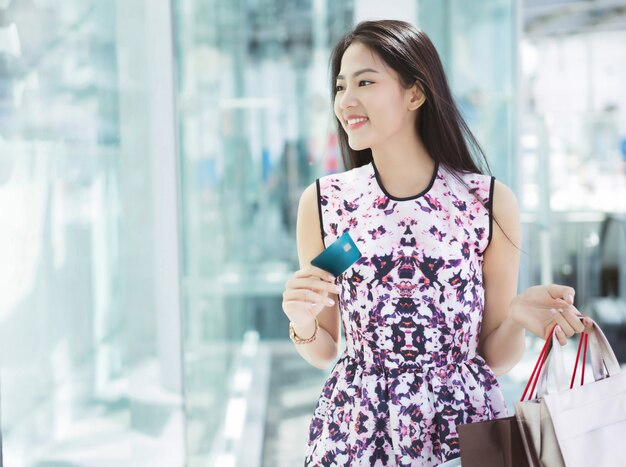 Azjatycka kobieta używa kredytową kartę dla robić zakupy w centrum handlowym