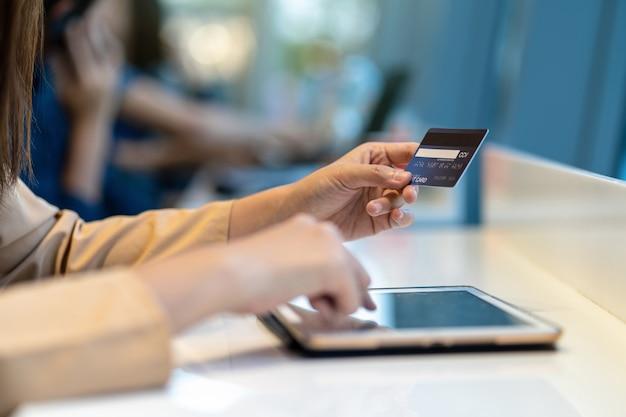 Azjatycka kobieta używa kredytową kartę z pastylką dla online zakupy w wydziałowym sklepie