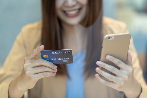 Azjatycka kobieta używa kredytową kartę z wiszącą ozdobą dla online zakupy