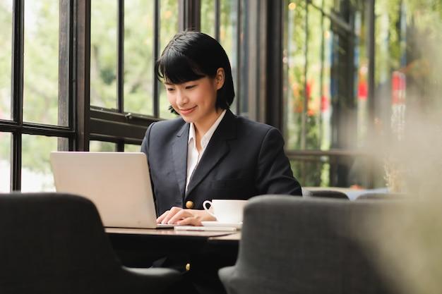 Azjatycka kobieta używa laptop i pijący kawę w sklep z kawą kawiarni