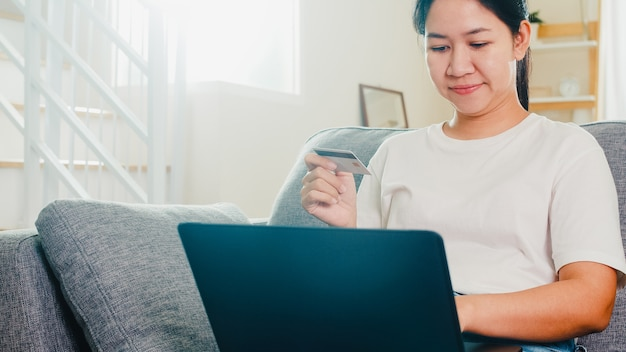 Azjatycka kobieta używa laptop, kredytowej karty zakup i zakupu handlu elektronicznego internet w żywym pokoju od domu