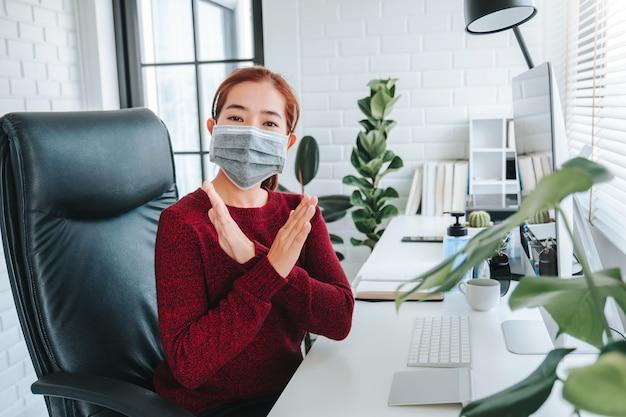 Azjatycka kobieta używa maskowego obsiadanie na biurowym biurku