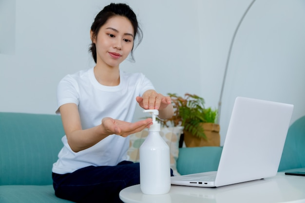 Azjatycka kobieta używa odkażacza do rąk w żelu alkoholowym