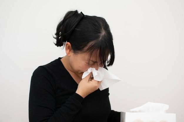 Azjatycka kobieta używa serwetkę, gdy kicha od zimna