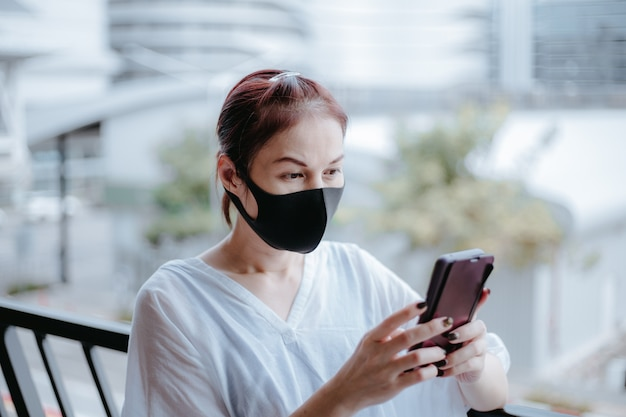 Azjatycka kobieta używa smartfona z maską medyczną na ulicy miasta.