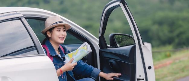 Azjatycka kobieta używa smartphone i mapę między napędowym samochodem na wycieczce samochodowej