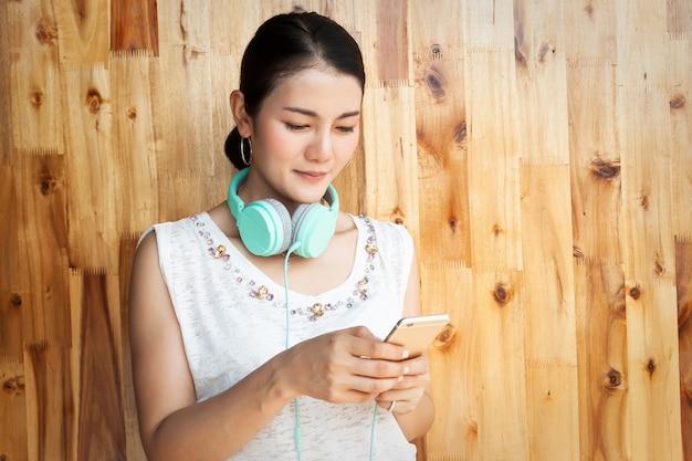 Azjatycka kobieta używa telefon komórkowego z hełmofonami na jej szyi