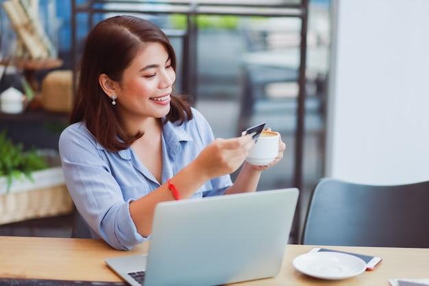 Azjatycka kobieta używa telefon komórkowego z kredytową kartą i laptopem dla robić zakupy online zapłatę w sklep z kawą kawiarni z przyjaciółmi