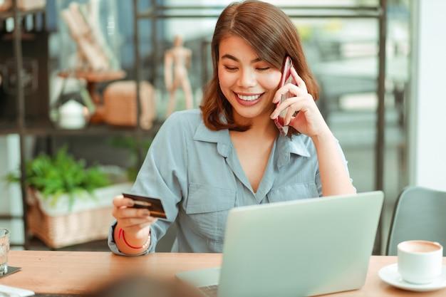Azjatycka kobieta używa telefon komórkowego z kredytową kartą i laptopem dla robić zakupy online zapłatę w sklep z kawą