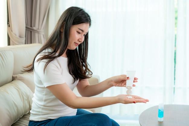 Azjatycka kobieta używająca balsamu lub nawilżająca jako dłoń do codziennego życia, aby ochronić skórę przed wysuszeniem i podrażnieniem po użyciu alkoholowego żelu antyseptycznego