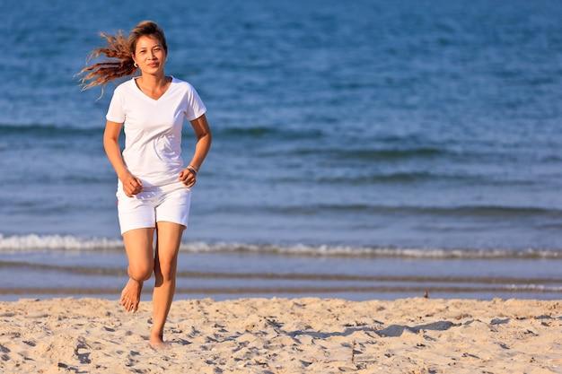 Azjatycka kobieta w białym ubraniu biegająca na tropikalnej plaży
