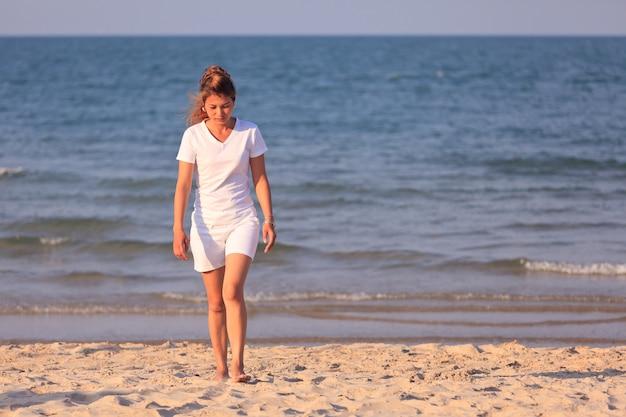Azjatycka kobieta w białym ubraniu spacerująca po tropikalnej plaży