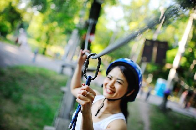 Azjatycka kobieta w błękitnego hełma wspinaczkowej arkanie