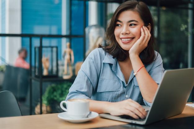 Azjatycka kobieta w błękitnej koszula w kawiarni pije kawę i opowiada z chłopiec przyjaciela uśmiechem i szczęśliwą twarzą