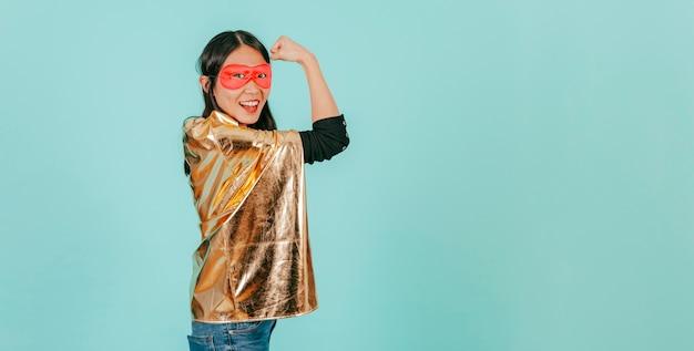 Azjatycka kobieta w bohatera kostiumowym pokazuje mięśni