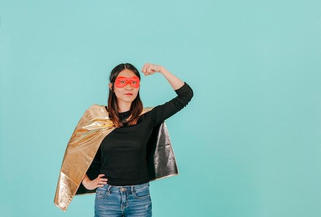 Azjatycka kobieta w bohatera kostiumu pokazuje bicepsy