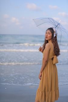 Azjatycka kobieta w brązowej sukni relaksuje się szczęśliwy. z wycieczką na plażę