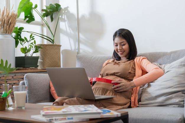Azjatycka kobieta w ciąży uśmiecha się i siedzi na kanapie i słucha muzyki oraz korzysta z laptopa z uczuciem szczęścia i relaksu.