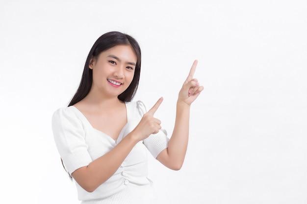 Azjatycka kobieta w czarnych długich włosach w białej koszuli stoi uśmiechając się grzecznie wskazując w górę