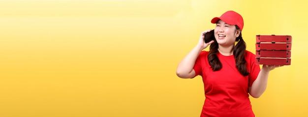 Azjatycka kobieta w czerwonej nakrętce, daje porządek jedzenia włoskiej pizzy w kartonowych pudełkach odizolowywał mienie telefon komórkowego.
