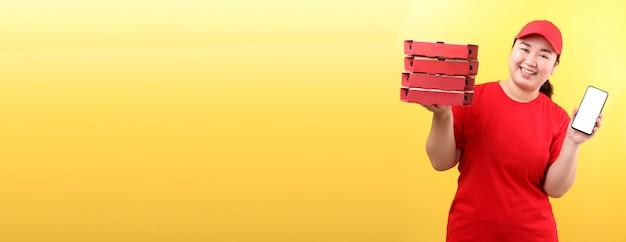 Azjatycka kobieta w czerwonej nakrętce, daje rozkazowi karmowemu włoskiej pizzy w kartonowych pudełkach odizolowywał mienie telefon komórkowego z pustego bielu pustym ekranem.