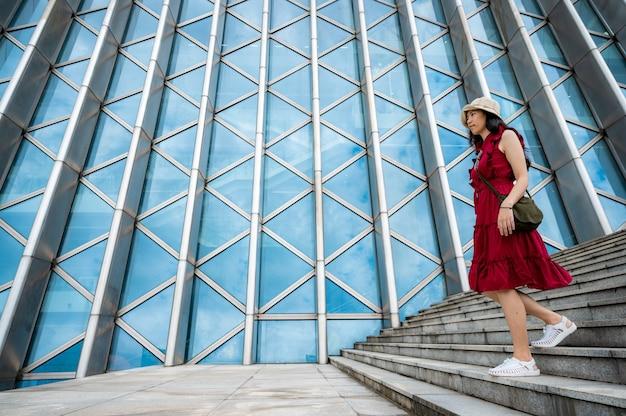 Azjatycka kobieta w czerwonej sukience w nowoczesnym budynku, dziewczyna z miejskiego stylu życia
