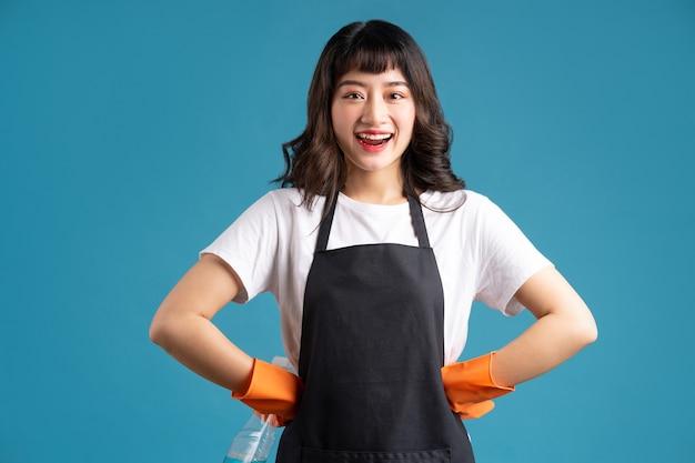 Azjatycka kobieta w fartuch i rękawiczki przygotowuje się do sprzątania