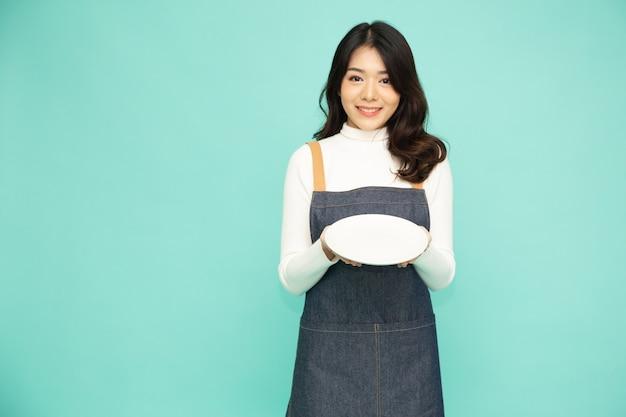Azjatycka kobieta w fartuch stojąc i trzymając pusty biały talerz lub naczynie na białym tle na zielonej ścianie