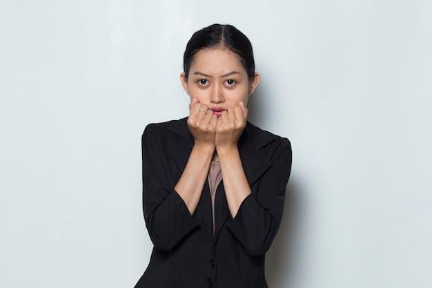 Azjatycka kobieta w formalnym stroju pozuje szokującą i zaskakującą akcję