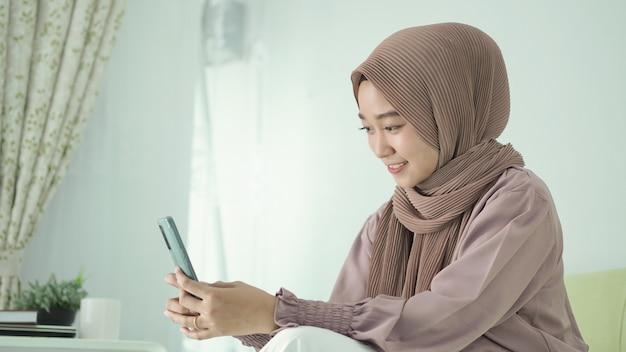 Azjatycka kobieta w hidżabie bawi się na telefonie bawiąc się w domu