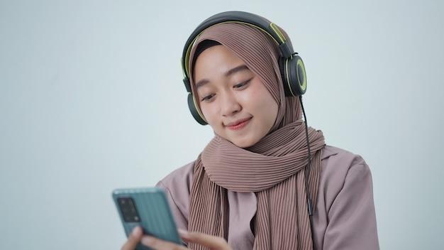 Azjatycka kobieta w hidżabie patrząca na ekran telefonu podczas słuchania w domu