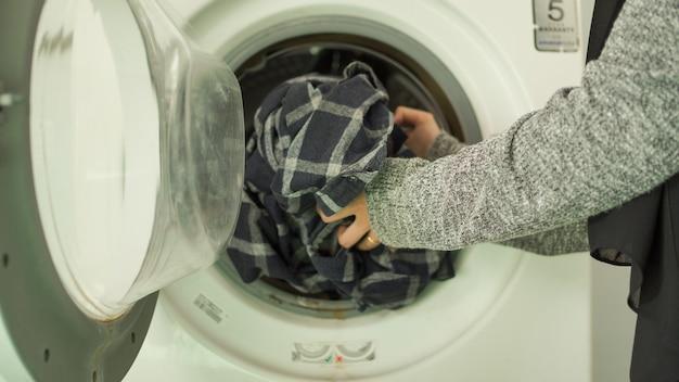 Azjatycka kobieta w hidżabie piorąca ubrania w pralce w domu