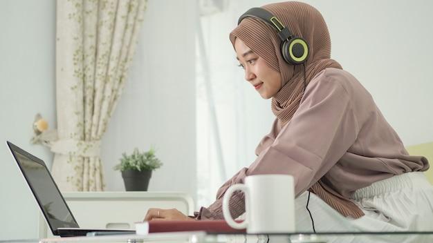 Azjatycka kobieta w hidżabie, pracująca w domu, z radością słuchająca