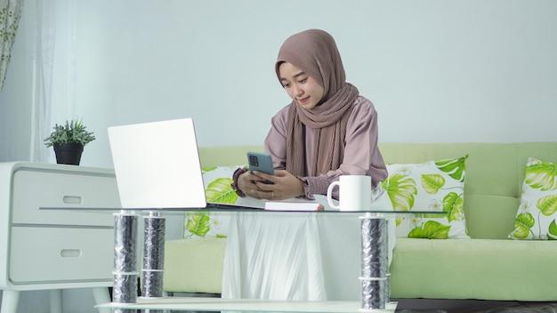 Azjatycka kobieta w hidżabie pracuje w domu i szuka pomysłów na swoim smartfonie