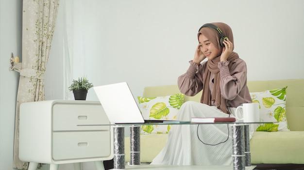 Azjatycka kobieta w hidżabie pracuje w domu, słuchając uważnie