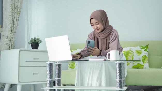 Azjatycka kobieta w hidżabie pracuje w domu, szukając pomysłów na ekranie swojego smartfona