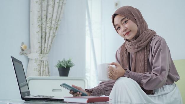 Azjatycka kobieta w hidżabie pracuje w domu, uśmiechając się i delektując się drinkiem